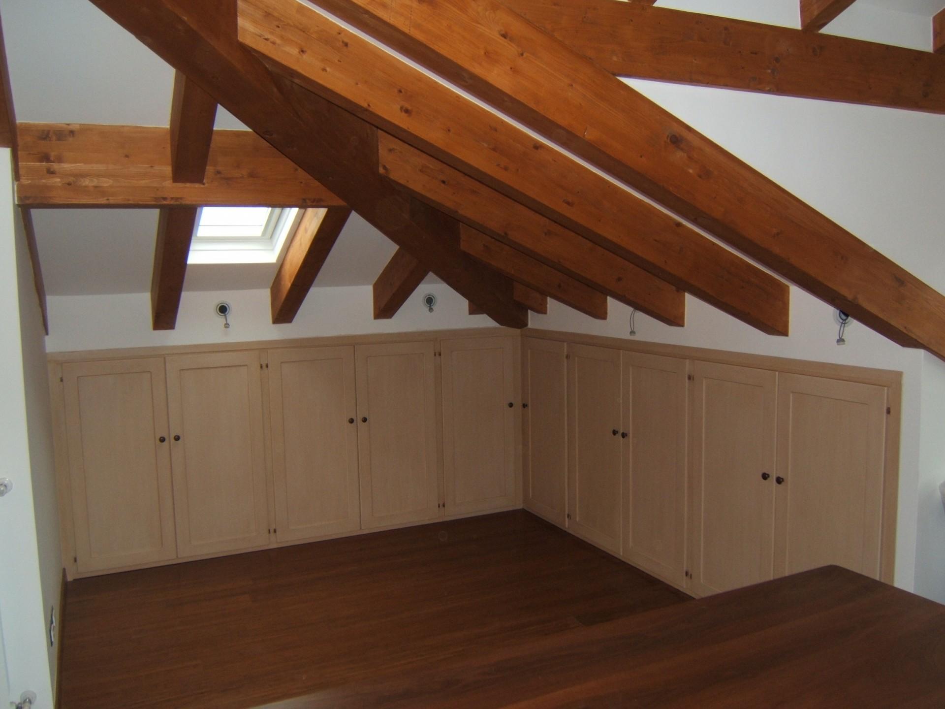 Arredamento di un sottotetto con armadi costruiti in legno su misura.