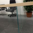 Tavolo in legno con gambe in vetro.
